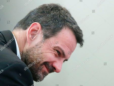 """Former trader Jerome Kerviel smiles in the Versailles appeal court, west of Paris, . A French court has cut the civil damages owed by former trader Jerome Kerviel from 4.9 billion euros ($5.5 billion) to 1 million euros ($1.1 million). Kerviel was """"partly responsible"""" for huge losses suffered in 2008 by the bank Societe Generale through his reckless financial trades"""