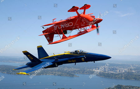 Stock Photo of Sean D. Tucker, Ryan Chamberlain. Aerobatic pilot Sean D. Tucker, top, flies inverted in his Team Oracle Challenger III biplane while in formation with U.S. Navy Lt. Ryan Chamberlain, the lead solo pilot for the Blue Angels, in a Boeing F/A-18 Hornet, near Seattle, . Tucker, the Blue Angels, and other aerobatic acts are in town to preform in the annual Seafair Air Show, which will take place Aug. 5-7 over Lake Washington in Seattle