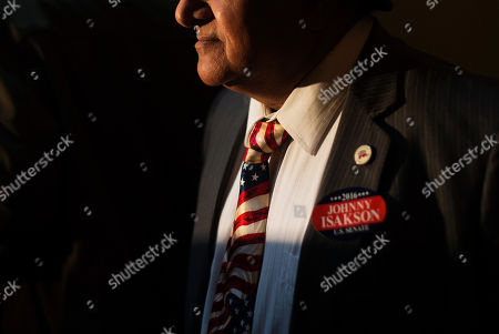 """Former Republican Congressional candidate Shahid Malik wears a tie decorated like the American flag and a sticker supporting Sen. Johnny Isakson, R-Ga., at a news conference where Isakson announced his re-election bid for the 2016 campaign at the state Capitol, in Atlanta. The Republican, who'll be seeking his third term, told about 200 supporters Monday that he wants to keep fighting to build up Georgia's infrastructure, pass a balanced budget amendment and reduce federal spending. Gov. Nathan Deal praised Isakson as a """"stable conservative leader"""