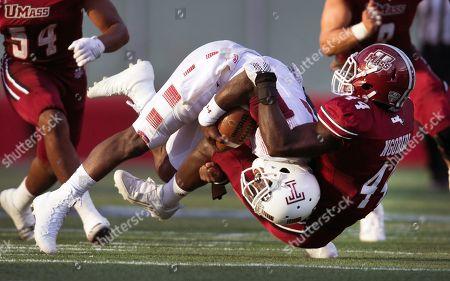 Peter Ngobidi, P.J. Walker. Massachusetts linebacker Peter Ngobidi (44) pulls down Temple quarterback P.J. Walker (11) in the second half of an NCAA college football game at Gillette Stadium in Foxborough, Mass