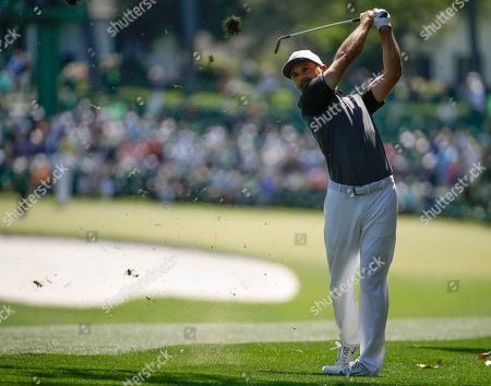 Trevor Immelman, of South Africa, hits on the first hole during the first round at the Masters golf tournament, in Augusta, Ga