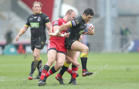 Bryson Goodwin of Warrington Wolves tries to escape from Salford Red Devils' Craig Kopczak and Salford Red Devils' Josh Wood