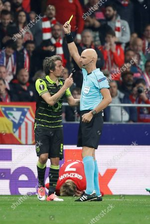 Sporting's Fabio Coentrao (L) protests a yellow card from referee Sergei Karasev (R) during the UEFA Europa League quarter final first leg soccer match between Atletico Madrid and Sporting CP at Wanda Metropolitano stadium in Madrid, Spain, 05 April 2018.