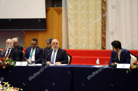 Stock Photo of Iraqi Prime Minister Haider al-Abadi (C) delivers an opening speech whuile his Japanese counterpart Shinzo Abe (R) and Iraqi Foreign Minister Ibrahim al-Jafari (L) look on as they attend the international conference on security in Iraq at a hotel in Tokyo on Thursday, April 5, 2018.