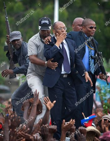 Stock Picture of Jean Bertrand Aristide. Flanked by body guards, former Haitian President Jean-Bertrand Aristide, center, greets supporters as he leaves the courthouse in Port-au-Prince, Haiti, . Aristide greeted a small group of onlookers after testifying before a judge investigating the slaying of one of the country's most prominent journalists. The judge is questioning Aristide about the 2000 killing of Jean Dominique, a friend of the former president