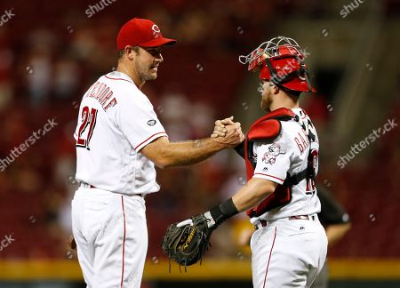 Cincinnati Reds relief pitcher Ross Ohlendorf (27) and catcher Tucker Barnhart celebrate their 8-2 win over the Atlanta Braves in a baseball game, in Cincinnati