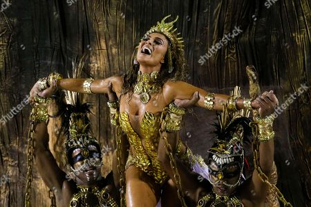 Actress Juliana Paes is carried by dancers of the Viradouro samba school in the Carnival parade at the Sambadrome in Rio de Janeiro, Brazil, . The skies opened up about an hour ahead of the start of the all-night-long extravaganza, drenching revelers and flooding streets near the Sambadrome
