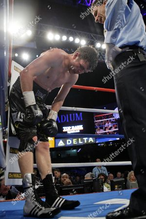 Yuri Foreman gathers him self after injuring his knee during the seventh round of a WBA light middleweight title match against Miguel Cotto as referee Arthur Mercante Jr. looks, at Yankee Stadium in New York. Foreman slipped in the seventh round and badly twisted his right knee, then slipped to the mat again later in the round. He survived to the end but could hardly move around the ring, limping on a right knee that was already covered by a black brace and getting tagged by Cotto at will