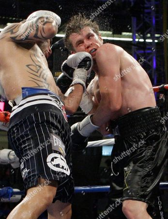 Miguel Cotto, Yuri Foreman. Yuri Foreman, right, is hit by Miguel Cotto, left, during the seventh round of a WBA light middleweight title match, at Yankee Stadium in New York. Cotto stopped Israel's Yuri Foreman in the ninth round Saturday night to win the junior middleweight title in the first fight at Yankee Stadium in more than three decades