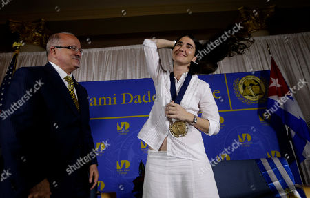Yoani Sanchez, Eduardo Padron. Blogger and activist Yoani Sanchez, of Cuba, right, adjusts her hair after receiving a medal from Miami Dade College president Eduardo Padron, left, after speaking at the Freedom Tower of Miami Dade College, in Miami. Sanchez has gained thousands of followers worldwide for her candid descriptions of modern life in Cuba on her blog Generation Y