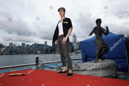 Hong Kong actor Aarif Lee poses in front of a statue of Bruce Lee during a promotional event in Hong Kong . Filmmakers have cast the rising star from Hong Kong to play Bruce Lee in an upcoming biopic that focuses on the late kung fu icon's youth