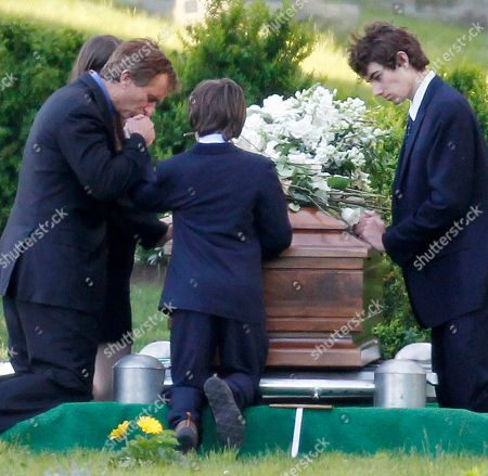 Robert F. Kennedy Jr., left, kneels with his children at the casket of Mary Richardson Kennedy, in St. Francis Xavier Cemetery in Centerville, Mass., . Mary Richardson Kennedy was found dead of an apparent suicide last week at her home in Bedford, N.Y