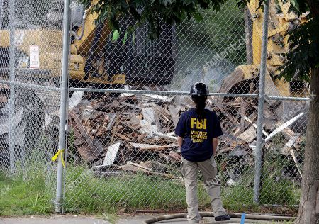 """An FBI agent watches as the house where three women were held captive and raped for more than a decade is being demolished, in Cleveland. Authorities want to make sure the rubble isn't sold online as """"murderabilia,"""" though no one died there. The house was torn down as part of a deal that spared Ariel Castro a possible death sentence. He was sentenced last week to life in prison plus 1,000 years. Castro apologized but blamed his addiction to pornography"""