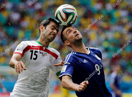 Iran's Pejman Montazeri, left, and Bosnia's Vedad Ibisevic battle for the ball during a group F World Cup soccer match between Bosnia and Iran at the Arena Fonte Nova in Salvador, Brazil
