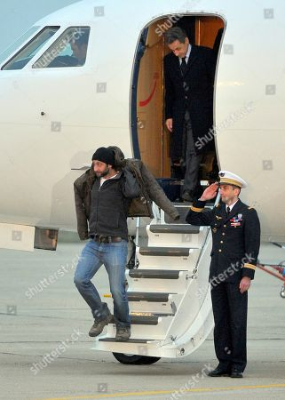 French photographer, William Daniels, bottom, followed by French President, Nicolas Sarkozy, alight from the plane carrying him and French reporter, Edith Bouvier, after they landed at the Villacoublay military airport, outside Paris, Friday, March 2nd, 2012. Two French journalists who were smuggled out of Syria have arrived in France. Edith Bouvier, who was injured, and William Daniels were caught up in a Syrian government siege of a rebel-held neighborhood in the city of Homs