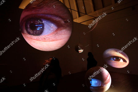"Visitors look at an art work by American artist Tony Oursler entitled ""Eyes"" displayed at a gallery in Beijing, China"