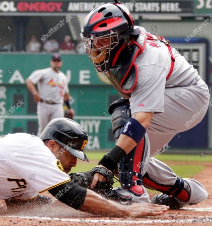 Stock Image of Yadier Molina, Derrek Lee. Pittsburgh Pirates' Derrek Lee, left, is tagged out by St. Louis Cardinals catcher Yadier Molina while attempting to score on an infield grounder by Pedro Alvarez during the second inning of a baseball game in Pittsburgh