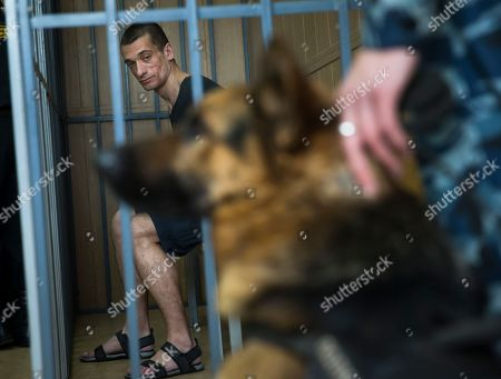 Russian artist Pyotr Pavlensky looks at a police dog while sitting in a cage in court room in Moscow, Russia, . The Russian court has ruled to free Pavlensky, who has been in detention since November after he set fire to the doors of the Russian security agency, the former KGB headquarters in Moscow, on Wednesday, June 8, 2016