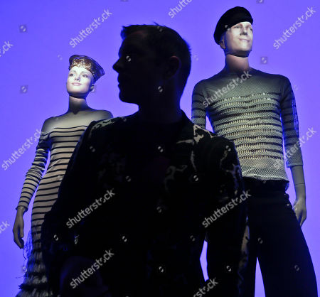 "Stock Image of Thierry-Maxime Loriot, center, is silhouetted between mannequins, one bearing his likeness at right, during the installation of fashion designer Jean Paul Gaultier's exhibit ""The Fashion World of Jean Paul Gaultier: From the Sidewalk to the Catwalk,"" on at the Brooklyn Museum in New York. Loriot is the curator of the first international exhibition dedicated to the groundbreaking French couturier, integrating multimedia around seven themes tracing his influences since he emerged as a designer in the 1970s"