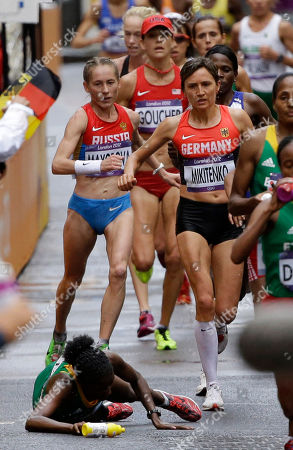 Ethiopia's gold medal winner Tiki Gelana falls during the women's marathon at the 2012 Summer Olympics in London. Right is Germany's Irina Mikitenko