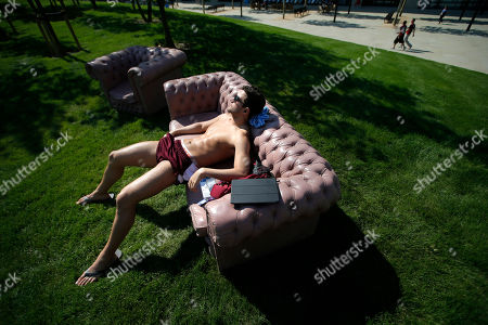 Stock Picture of Amini Fonua, a swimmer from Tonga, sunbathes at the Athletes' Village at the Olympic Park, in London. Opening ceremonies for the 2012 London Olympics will be held Friday, July 27