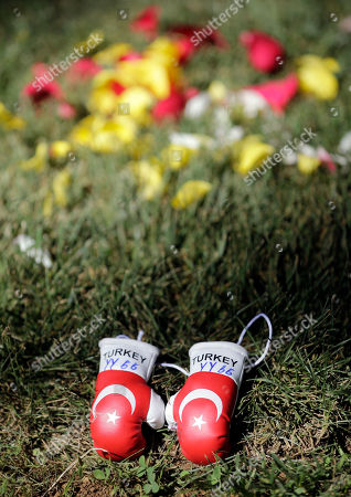 Miniature boxing gloves left by Yusuf Anac, a Turk now living in Bochum, Germany, lie on the grave of boxing great Muhammad Ali, in Louisville, Ky. Cave Hill Cemetery opened to the public Saturday, the day after Ali's burial