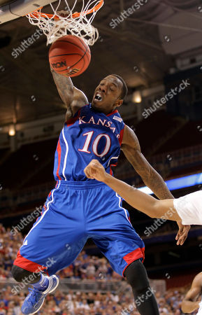 Kansas guard Tyshawn Taylor (10) dunks during the second half of the NCAA men's college basketball tournament Midwest Regional final against North Carolina, in St. Louis