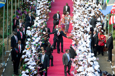 Michelle Obama, Salma Kikwete, Jakaya Kikwete, Barack Obama. President Barack Obama and Tanzanian President Jakaya Kikwete walk in front of first lady Michelle Obama and Tanzanian first lady Salma Kikwete greeting the cheering crowd as they arrive at the State House in Dar es Salaam, Tanzania
