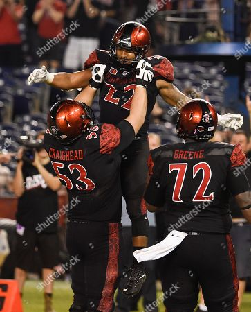 Chase Price, Robert Craighead. San Diego State running back Chase Price (22) is lifted up by San Diego State offensive lineman Robert Craighead (53) after scoring a touchdown during the second half of an NCAA college football game against Utah State, in San Diego