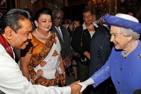 Britain's Queen Elizabeth II, right, shakes hands with Sri Lanka President Mahinda Rajapaksa, left, as his wife Shiranthi Rajapaksa, center, looks, during a reception prior to a lunch with Commonwealth Nations Heads of Government and representatives of the Commonwealth nations in central London