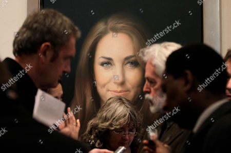 Members of the media talk to artist Paul Emsley, center right, in front of his newly-commissioned portrait of Kate, Duchess of Cambridge, on display at the National Portrait Gallery in London