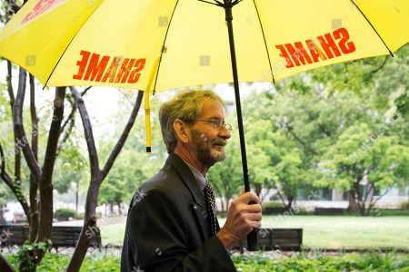 """Doug Hughes. Carrying an umbrella that says """"shame"""" on it, Douglas Hughes of Florida arrives at federal court in Washington, . Hughes, who flew a gyrocopter through some of America's most restricted airspace before landing at the Capitol pleaded not guilty on Thursday to the six charges he faces"""