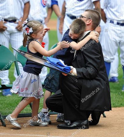 Katie Wood, Justin Wood, Kerry Wood. Katie Wood and her brother Justin hug their father, Chicago Cubs pitcher Kerry Wood, after he announced his retirement from baseball during a news conference at Wrigley Field, in Chicago