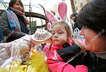 Dace Anderson, right, of Latvia, holds her daughter Ava, 4, close to a dog named Coco Chanel for a kiss that hopefully will stem Ava's tears during the annual Easter parade near St. Patrick's Cathedral, in New York