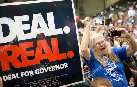 Linda Hepburn, of Villa Rica, Ga., a supporter of Democratic candidate for Georgia governor Jason Carter, shouts as a supporter for Republican candidate Gov. Nathan Deal holds up a sign during the gubernatorial debate, in Perry, Ga