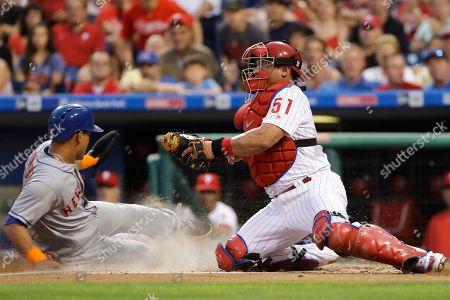 Carlos Ruiz, Juan Lagares. New York Mets' Juan Lagares, left, scores past Philadelphia Phillies catcher Carlos Ruiz on a sacrifice fly by Jose Reyes during the third inning of a baseball game, in Philadelphia