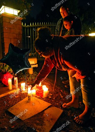 Cecy Robles places candle and a balloon in front of what is believed to be the home of singer Jenni Rivera as Ruben Robles, top, and Anthony Robles watch, in the Encino section of Los Angeles. The wreckage of a small plane believed to be carrying Rivera, the U.S-born singer whose soulful voice and unfettered discussion of a series of personal travails made her a Mexican-American superstar, was found in northern Mexico on Sunday. Authorities said there were no survivors