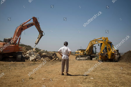A Jewish settler boy looks at earth-moving equipment working at a construction site in the West Bank Jewish settlement of Ariel, . Senior Palestinian official Yasser Abed Rabbo said Monday that President Mahmoud Abbas remains ready to walk out on Mideast peace talks if Israel resumes construction in its West Bank settlements now that building restrictions have expired