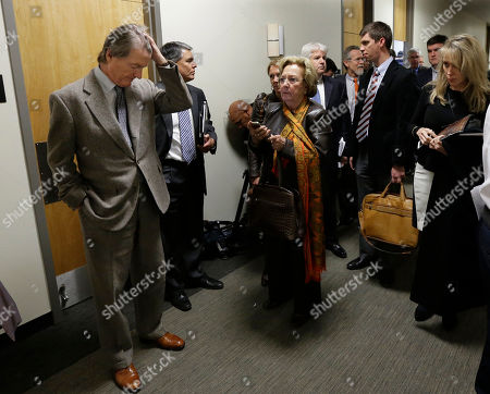 University of Texas at Austin President Bill Powers, left, waits to return to a UT Board of Regents meeting, in Austin, Texas. After Chancellor Francisco Cigarroa backed Powers, the regent board declined to act against the Austin campus leader