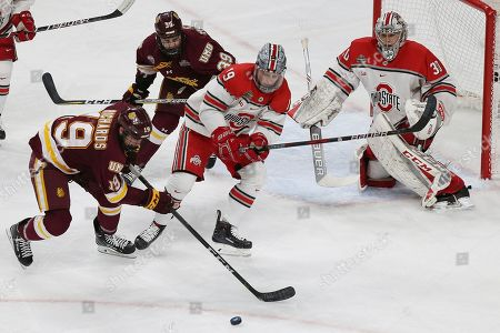 Minnesota Duluth's Justin Richards (19) controls the puck outside of the net against Ohio State during the second period of a semifinal in the NCAA men's Frozen Four hockey tournament, in St. Paul, Minn. Minnesota Duluth won 2-1