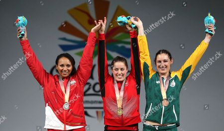 Canada's Women's 63Kg Weightlifting Gold medalist Maude Charron, center, with England's Silver medalist Zoe Smith and South Africa's Bronze medalist Mona Pretorius wave after the medal ceremony at the Commonwealth Games in Gold Coast, Australia
