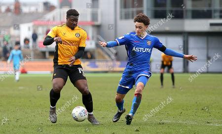 Tyler Reid of Newport County is tackled by Luke Amos of Stevenage.