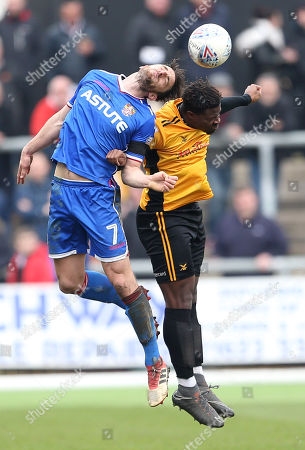 Chris Whelpdale of Stevenage and Tyler Reid of Newport County go up for the ball.