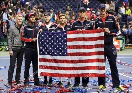 Jack Sock, Ryan Harrison, Sam Querrey, John Isner, Steve Johnson, Jim Courier. The United States Davis Cup tennis team poses with an American flag after beating Belgium to win their quarterfinal series, in Nashville, Tenn. From left are captain Jim Courier, Steve Johnson, Jack Sock, Ryan Harrison, Sam Querrey and John Isner