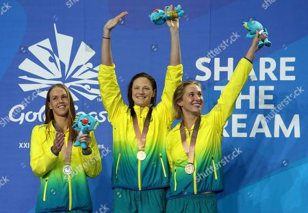 Cate Campbell, Holly Barrett, Madeline Groves. Women's 50m butterfly gold medalist Australia's Cate Campbell, centre, waves with compatriots Holly Barrett, silver, left, and Madeline Groves, bronze, on the podium at the Aquatic Centre during the 2018 Commonwealth Games on the Gold Coast, Australia