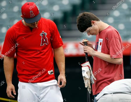 Michael London, Mike Trout. Visually impaired Michael London of Sacramento, Calif., inspects a bat given to him by Los Angeles Angels' Mike Trout, left, during warmups before a baseball game against the Oakland Athletics in Anaheim, Calif