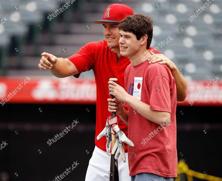 Mike Trout, Michael London. Los Angeles Angels' Mike Trout, left, poses for a photographer with visually impaired Michael London of Sacramento, Calif, after Trout gave him his bat during warmups before the team's baseball game against the Oakland Athletics in Anaheim, Calif