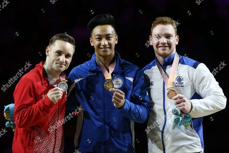 Stock Photo of Gold medalist Marios Georgiou of Cyprus, center, pose for photographers with silver medalist Morgan Scott of Canada, left, and bronze medalist Daniel Purvis of Scotland competes on the floor after the artistic gymnastics men's apparatus final at Coomera Indoor Stadium during the Commonwealth Games on the Gold Coast, Australia