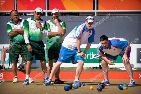 Stock Image of Hadyn Evans, Philip Jones, Ryan Dixon, Ronald Duncan, Derek Oliver. From left, second Hadyn Evans, lead Philip Jones, and skip Ryan Dixon of Norfolk Island, and lead Ronald Duncan and second Derek Oliver of Scotland watch the action during their men's triples semifinal lawn bowling match at the Broadbeach Bowls Club during the 2018 Commonwealth Games on the Gold Coast, Australia, . The Norfolk team won the bronze medal with a 19-16 victory over Canada, securing the island's second medal ever at the Commonwealth Games