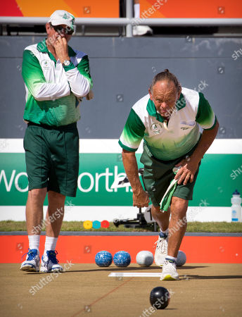 Stock Image of Hadyn Evans, Philip Jones. Second Hadyn Evans of Norfolk Island, right, bowls as lead Philip Jones watches during their men's triples semifinal lawn bowling match against Scotland at the Broadbeach Bowls Club during the 2018 Commonwealth Games on the Gold Coast, Australia, . The Norfolk team won the bronze medal with a 19-16 victory over Canada, securing the island's second medal ever at the Commonwealth Games
